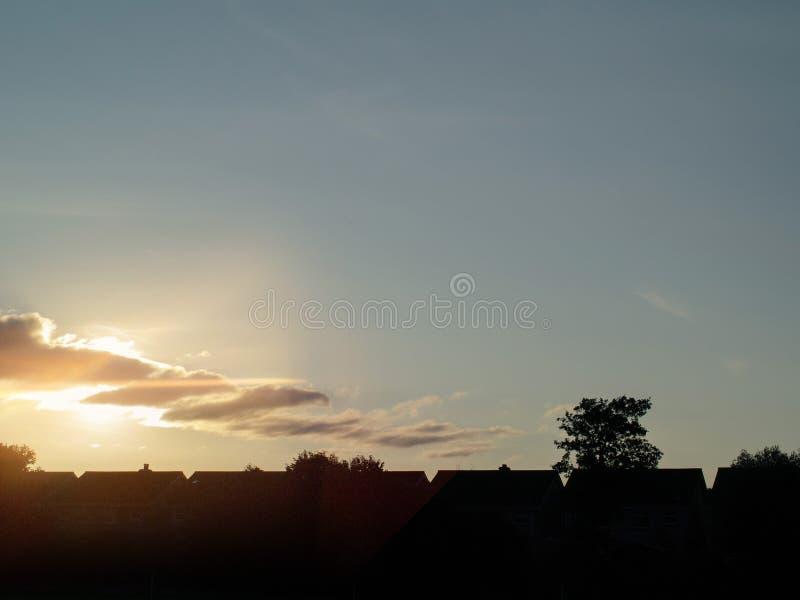 Zonsondergangtijd, Stedelijk gebied, de dakensilhouetten van het Huis tegen blauwe hemel Conceptenurbanisatie stock foto