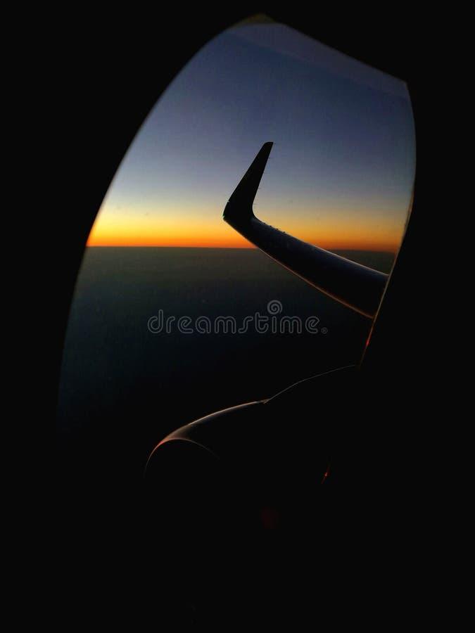 Zonsondergangwolken op horizon van vliegtuigvenster stock afbeeldingen