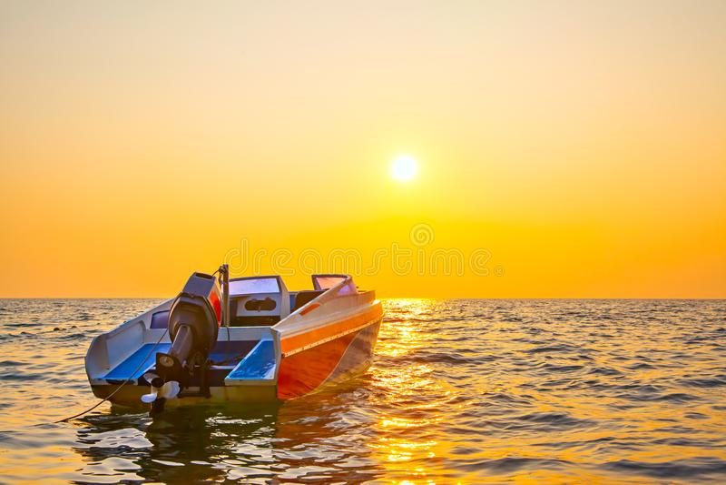 Zonsondergangzeegezicht met een motorboot stock foto