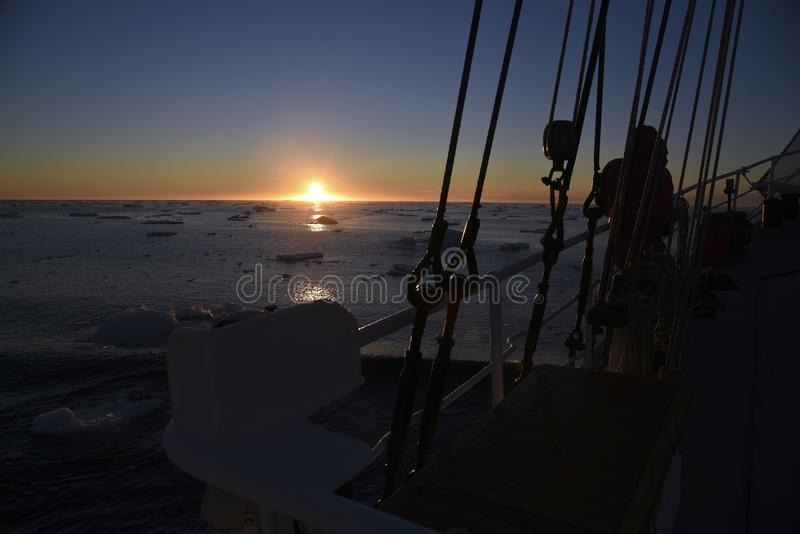 Zonsopgang bij het noordpooloverzees met een zeilboot vooraan stock fotografie