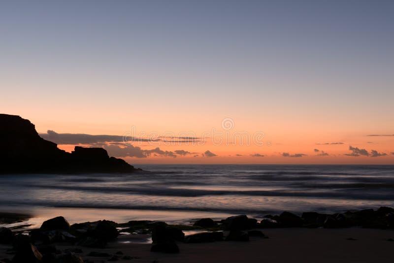 Zonsopgang bij het strand en de rotsen stock afbeelding