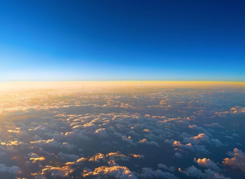 Zonsopgang boven wolken van een vliegtuigvenster Abstracte aardbedelaars stock foto's