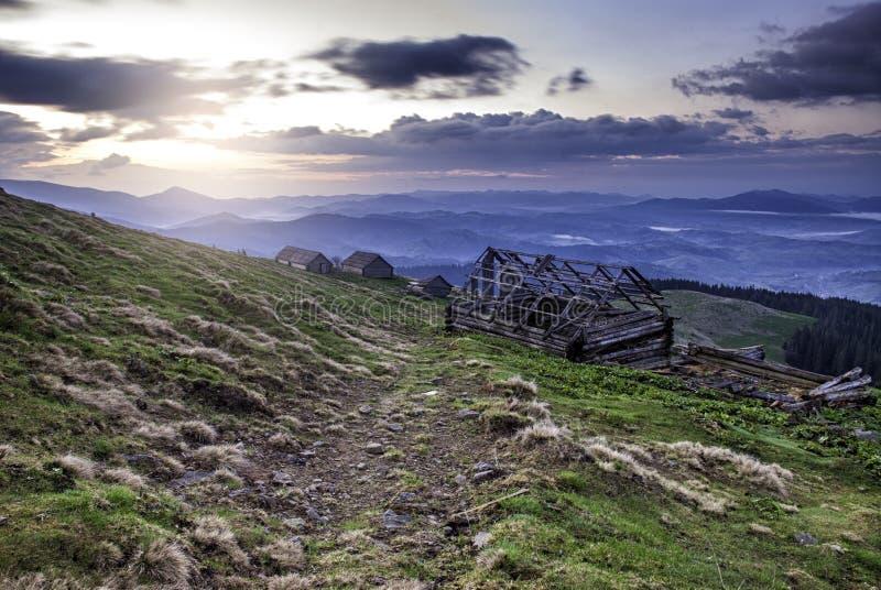 Zonsopgang in de Oekraïense Karpaten met weg en verlaten houten royalty-vrije stock fotografie