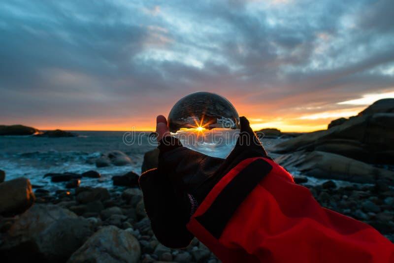 Zonsopgang in Eftang, Larvik, Noorwegen met kristallen bol stock afbeeldingen