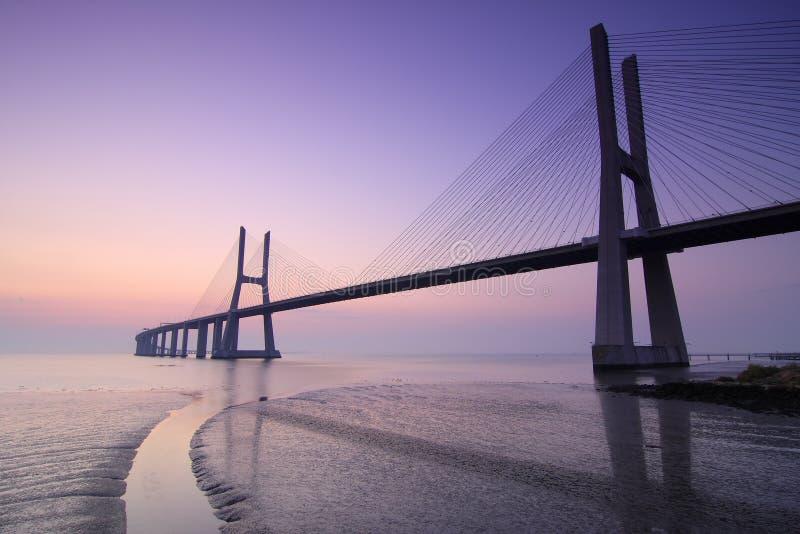 Zonsopgang en brug over Tagus-rivier in Lissabon Portugal stock afbeeldingen