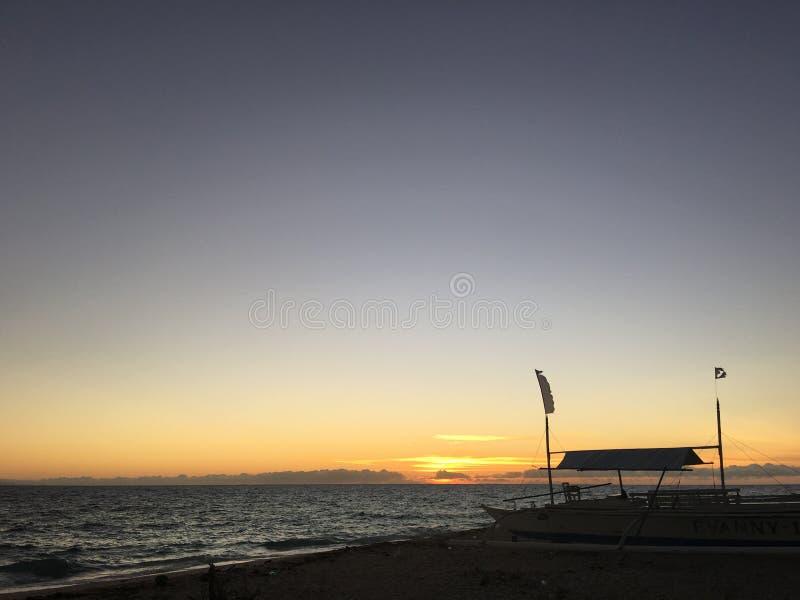 Zonsopgang en catamaranboot bij het strand stock foto