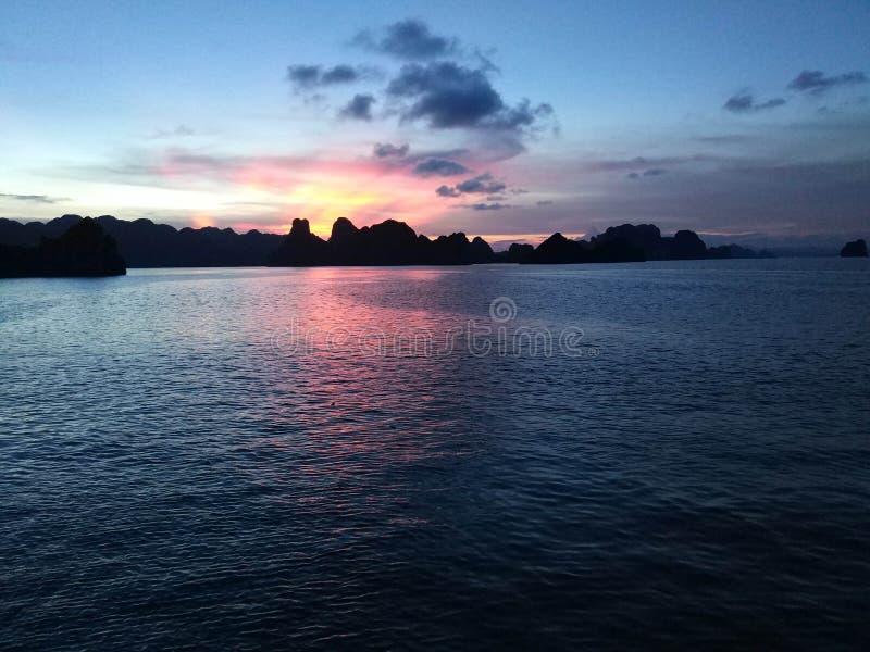Zonsopgang in Halong-Baai Met blauwe en oranje tonen Met sommige schepen bij achtergrond stock fotografie