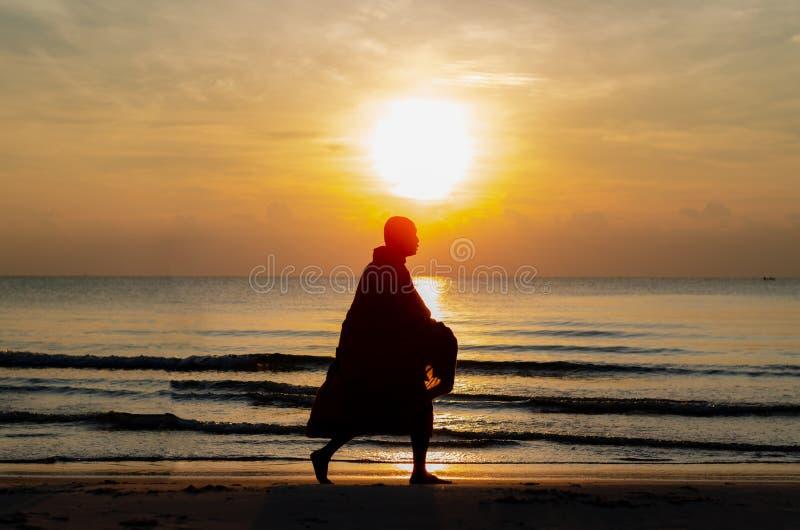 Zonsopgang met bezinning over het overzees en het strand die silhouetfoto van boeddhistische monnik hebben stock foto's