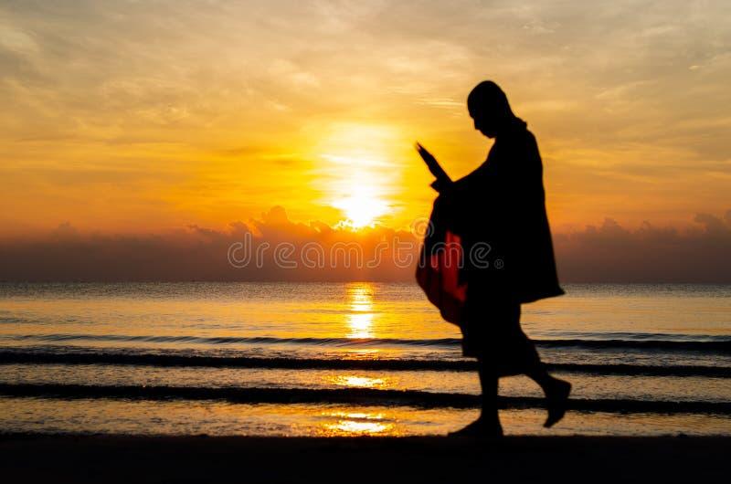 Zonsopgang met bezinning over het overzees en het strand die silhouetfoto van boeddhistische monnik hebben vertroebeld stock afbeeldingen