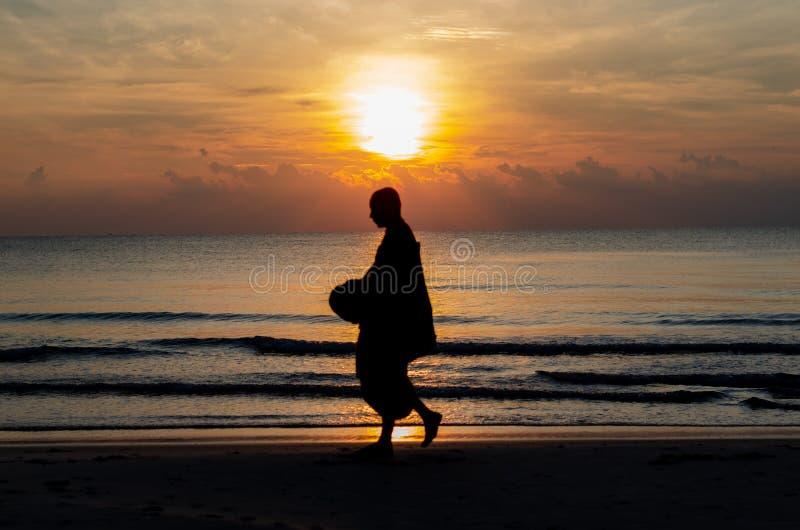 Zonsopgang met bezinning over het overzees en het strand die silhouetfoto van boeddhistische monnik hebben vertroebeld royalty-vrije stock foto's