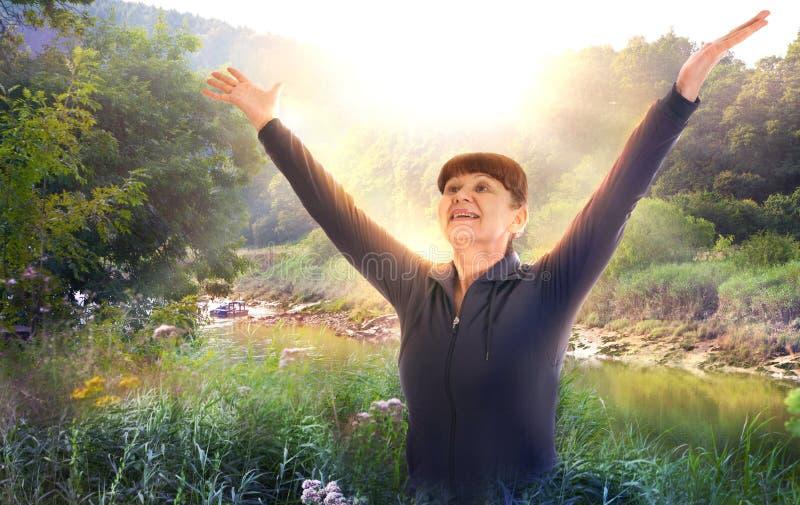 Zonsopgang, mooi park en gelukkige vrouw die haar handen tot de zon opheffen royalty-vrije stock foto
