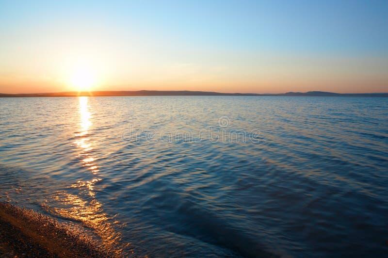 Zonsopgang op blauw water stock afbeelding
