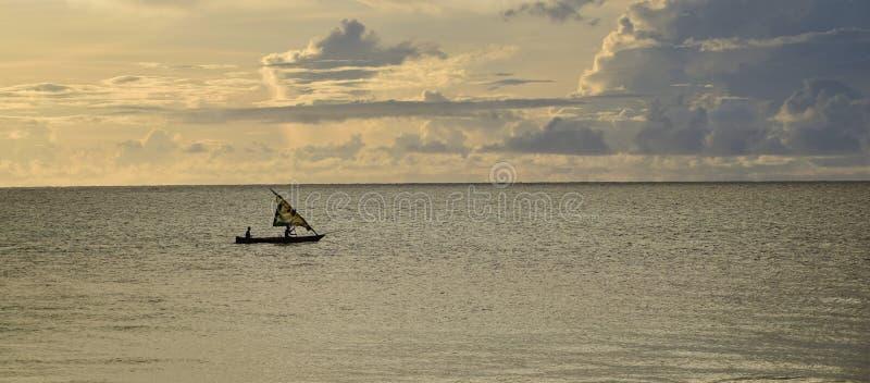 Zonsopgang over de Indische Oceaan Zeilboot onder gele, bewolkte hemel royalty-vrije stock afbeelding