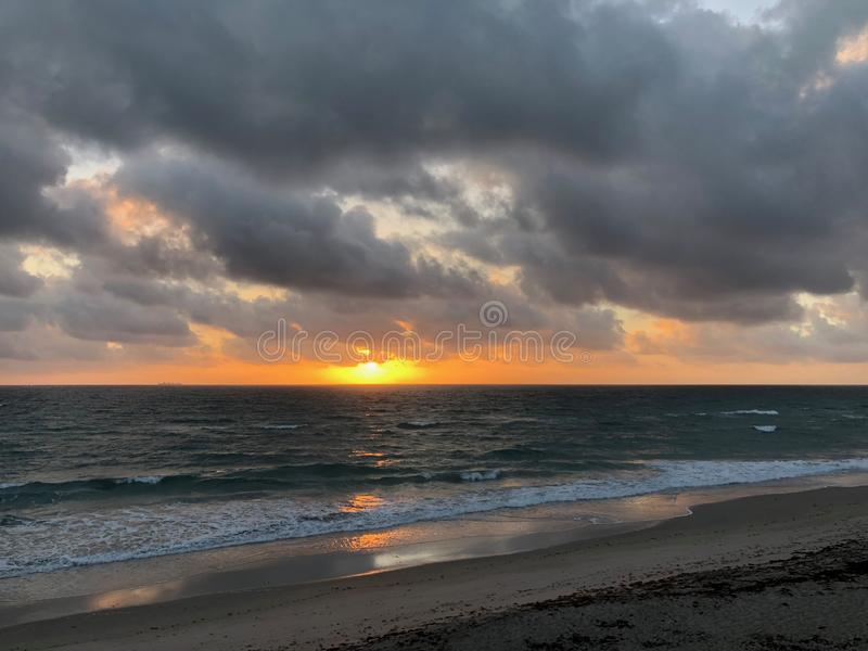 Zonsopgang over de oceaan met donkere wolken stock afbeeldingen