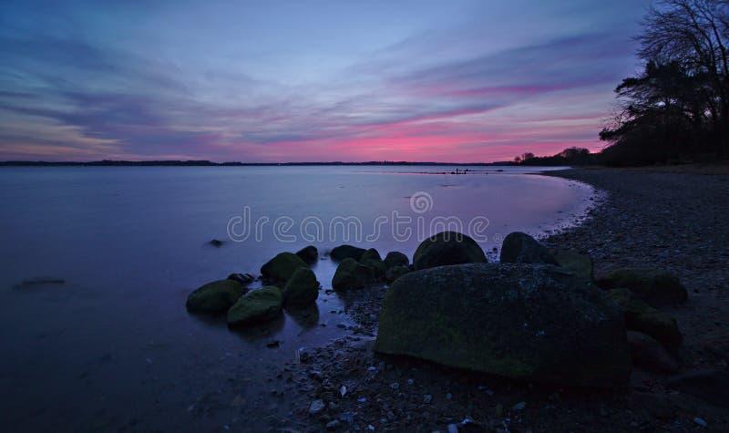Zonsopgang over de Oostzee met rotsen en kiezelsteenstrand in de voorgrond royalty-vrije stock fotografie
