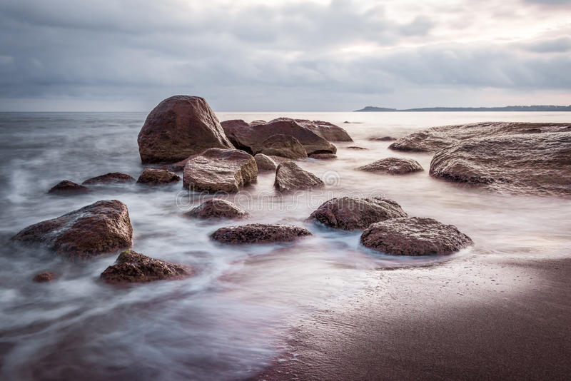 Zonsopgang over de overzeese rotsen op het strand Vlotte wateren, lang blootstellingseffect Zeegezicht in mooie blauwe en purpere stock foto's