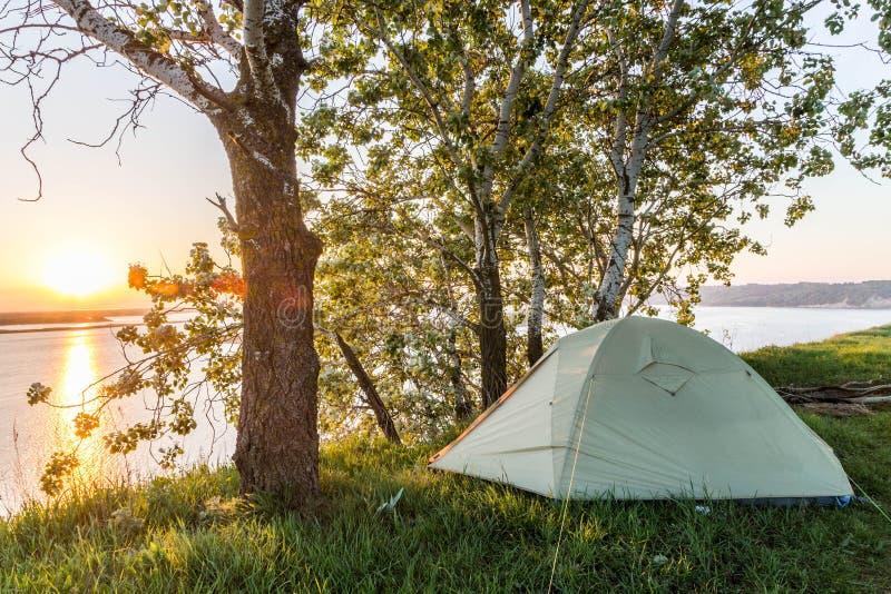 Zonsopgang over de rivier De tent van de toerist Rivierbank traveling stock afbeeldingen