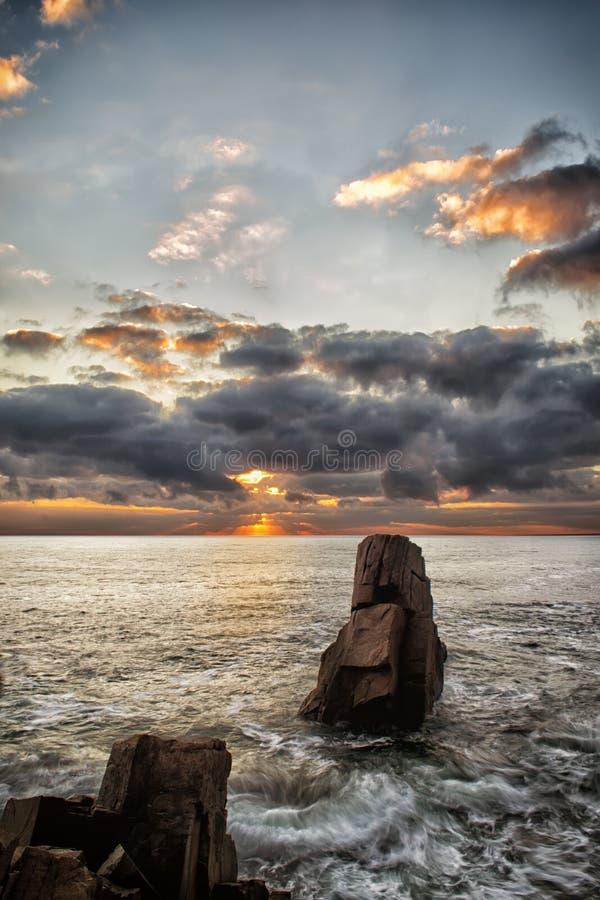 Zonsopgang over een rotsachtig strand Kleurrijke wolken die in het overzees nadenken Dramatische zonsopgang over de Zwarte Zee, B stock afbeeldingen