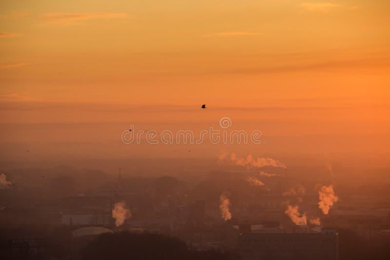 Zonsopgang over fabriek bij de industriezone de lichte stralen komt door ochtendmist en rook uit pijpen Chemische productie royalty-vrije stock foto