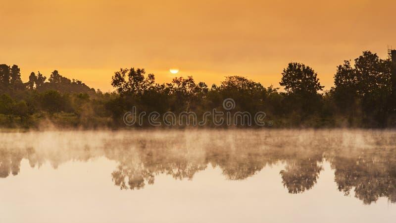 Zonsopgang over het meer met de bezinning stock afbeeldingen