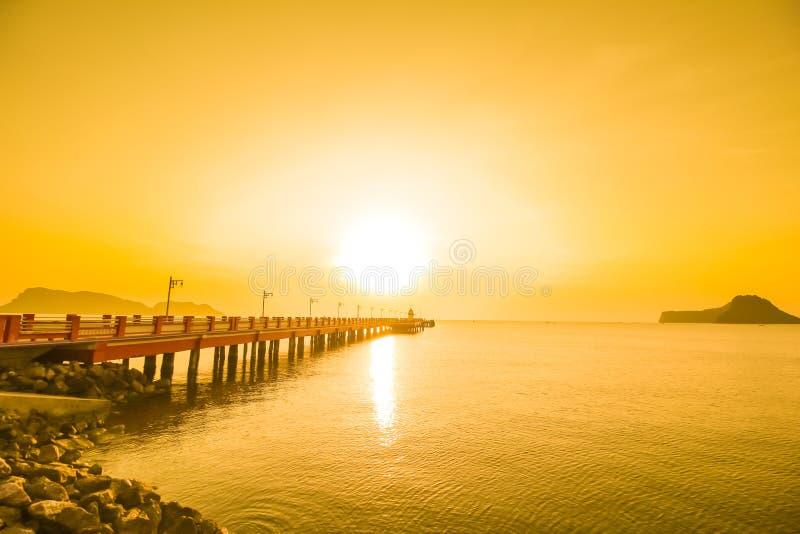 Zonsopgang over het overzees met brug en vuurtoren stock foto