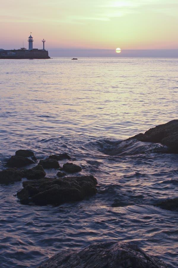 Zonsopgang over het overzees met de vuurtoren op de achtergrond stock fotografie