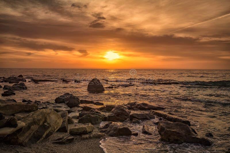 Zonsopgang over het overzees met rotsachtige kust royalty-vrije stock afbeelding