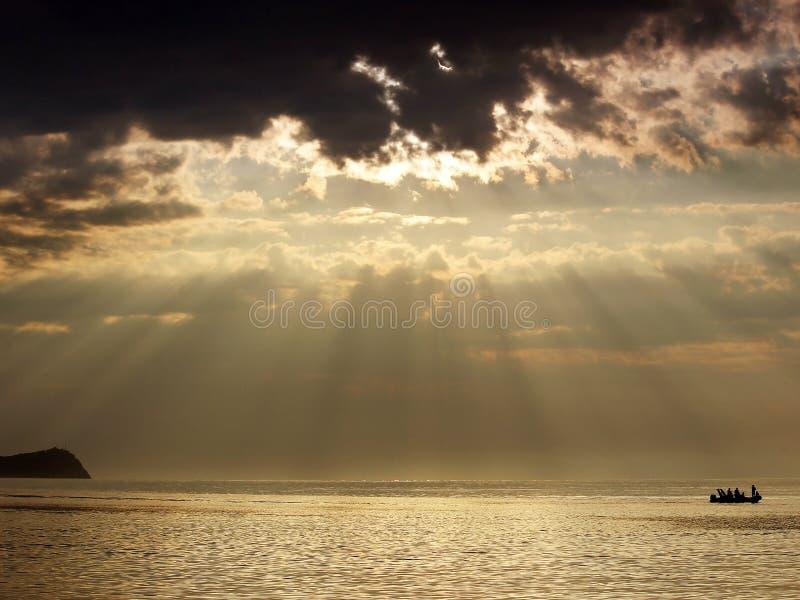 Zonsopgang over het overzeese en bootsilhouet De zon` s stralen glanzen radiaal door de wolken royalty-vrije stock foto's