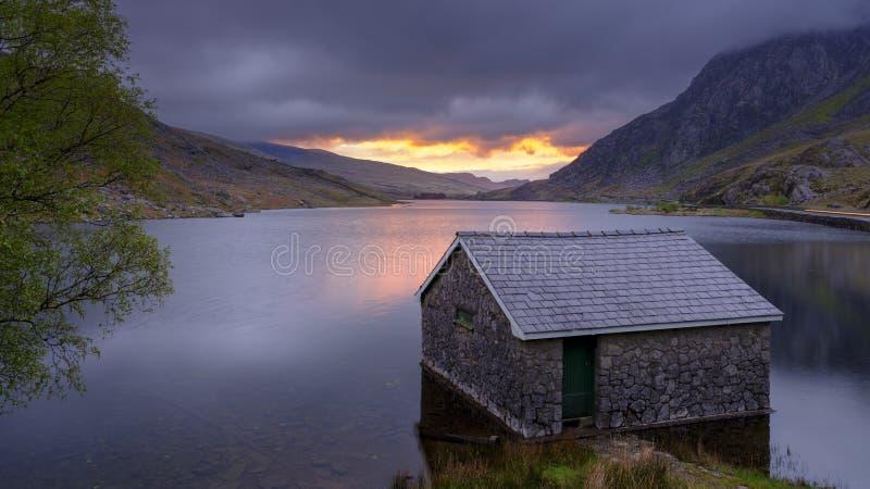 Zonsopgang over Llyn Ogwne en botenhuis, het Nationale Park van Snowdonia, Wales, het UK stock afbeeldingen