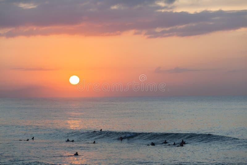 Zonsopgang van de surfers de Oceaangolf stock foto's