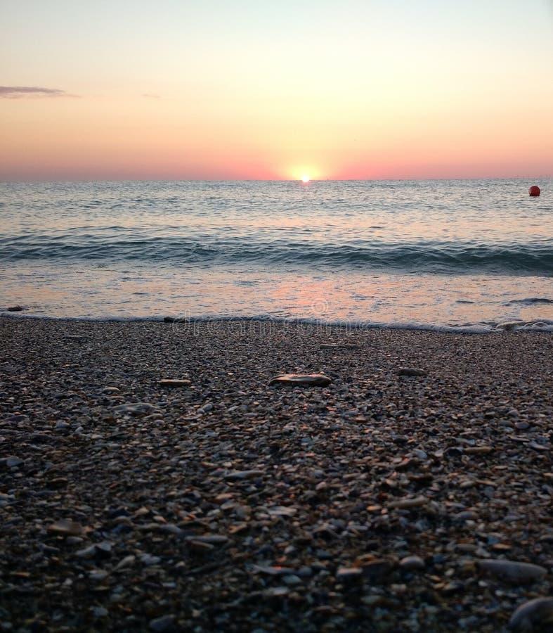 Zonsopgang van een strand wordt door overzeese golven wordt meegesleept gezien die stock afbeeldingen