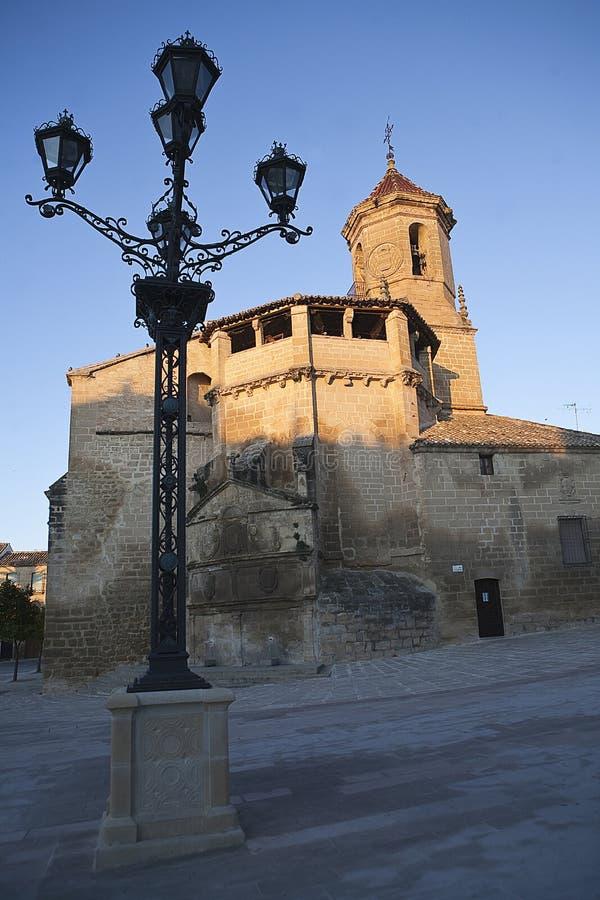 Zonsopgang in vierkant op 1 Mei, met zijvoorzijde en bron van de kerk van San Pablo en lantaarnpaal, Ubeda royalty-vrije stock foto's