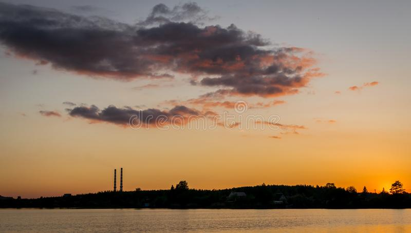Zonsopgang of zonsondergang dichtbij een meer met industriële schoorstenen stock afbeeldingen