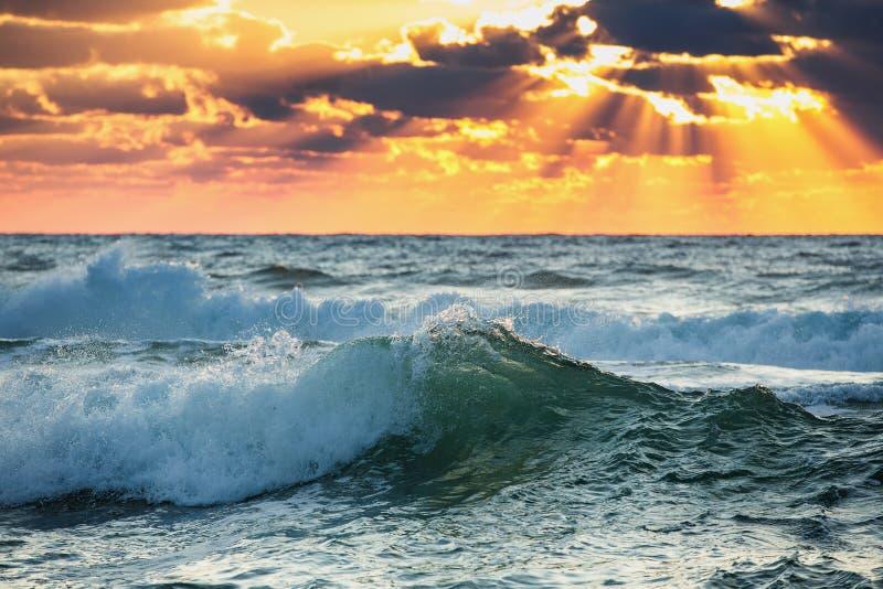 Zonsopganggolf Kleurrijke oceaanstrandzonsopgang met diepe blauwe hemel en zonstralen royalty-vrije stock afbeelding