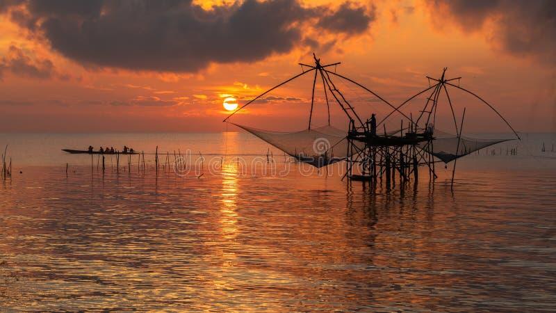 Zonsopganghemel met visser op vierkante onderdompeling netto en toerismeboot bij Pakpra-dorp stock afbeelding