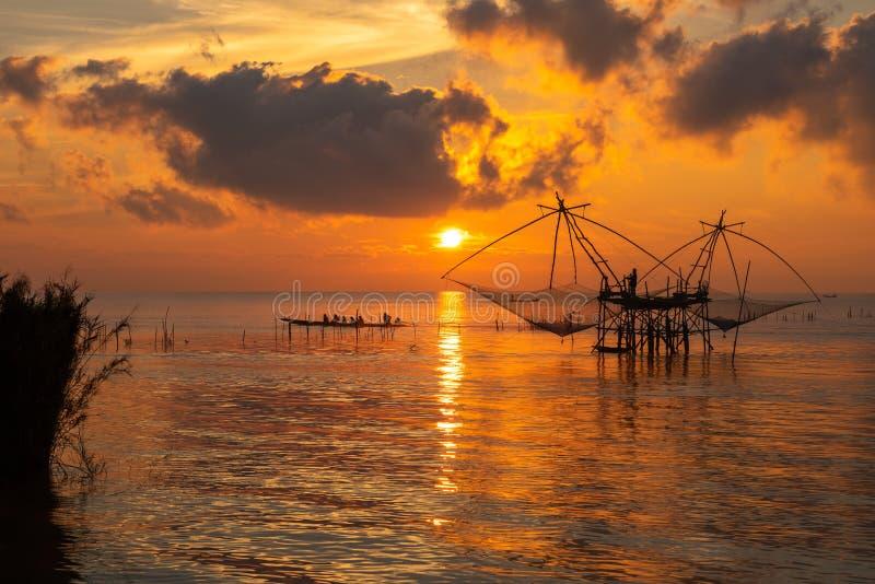 Zonsopganghemel met visser op vierkante onderdompeling netto en toerismeboot bij Pakpra-dorp stock fotografie