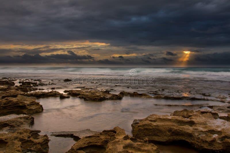 Zonsopganglandschap van oceaan met golvenwolken en rotsen stock afbeelding