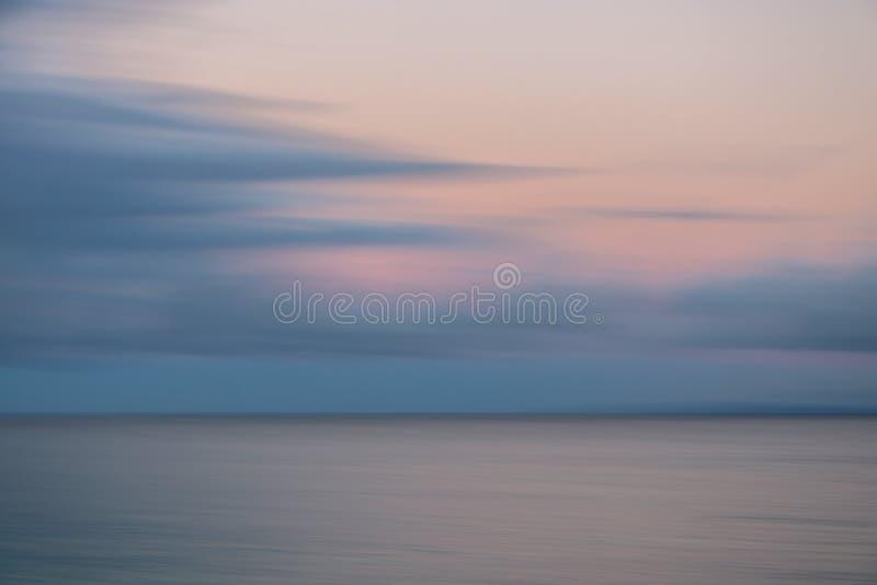 Download Zonsopgangroze En Grey Clouds Over Silver Ocean-Motieonduidelijk Beeld Stock Foto - Afbeelding bestaande uit rust, over: 107703662