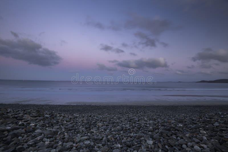Zonsopgangwolken over Kiezelsteenstrand in Wales, het UK stock afbeeldingen