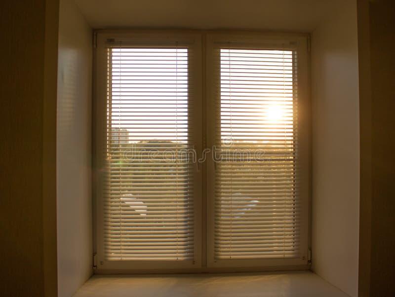 zonstijging achter de vensterzonneblinden en de gordijnenschaduwen stock foto's