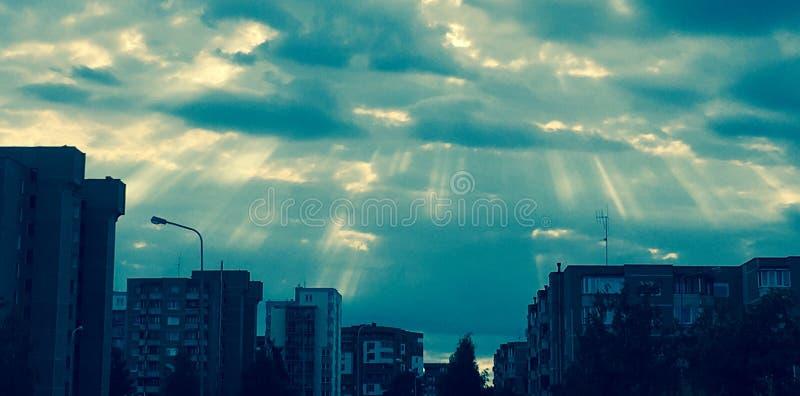 Zonstralen door wolken stock afbeeldingen