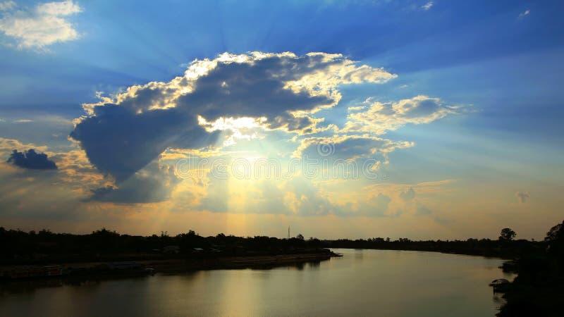 zonstralen door wolken bij zonsondergang royalty-vrije stock afbeeldingen