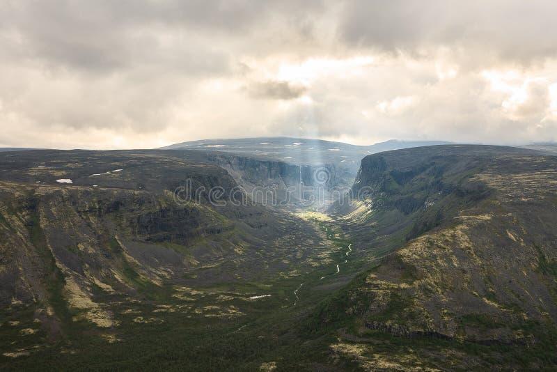 Zonstralen door wolken over een berg stock afbeelding