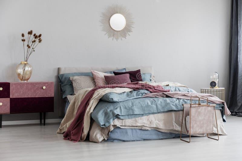 Zonvorm zoals spiegel op lege exemplaar ruimte grijze muur van eigentijds slaapkamerbinnenland met comfortabel bed stock foto's