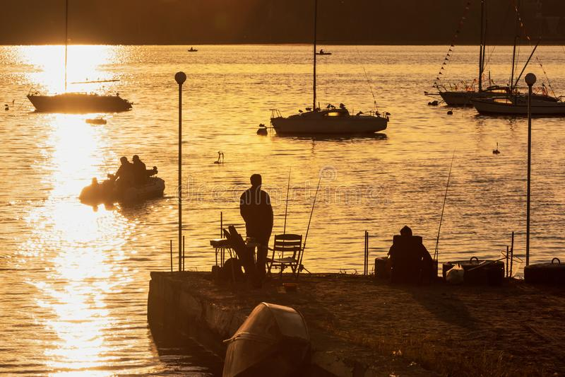 Zonweg, pijler met vissers stock fotografie