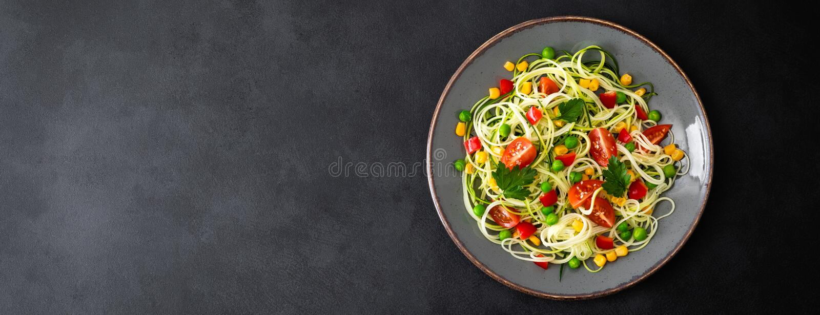 Zoodlie, healthy vegan food - zucchini noodlie with fresh green peas, tomato, bell pepper and corn for lunch royalty free stock photo