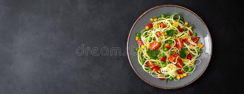 Zoodlie, zdrowy weganinu jedzenie - zucchini noodlie z świeżymi zielonymi grochami, pomidorem, dzwonkowym pieprzem i kukurudzą dl zdjęcie royalty free