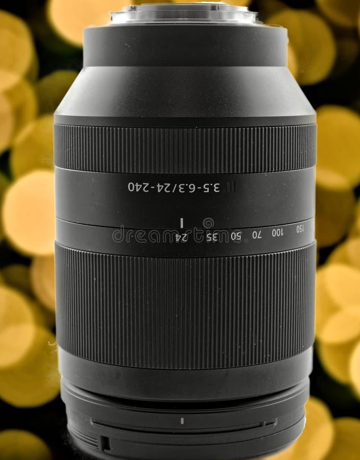 Zoom con una lunghezza focale di 24 - 240 millimetri davanti ad un fondo con bokeh giallo ed arancio, isolata fotografia stock
