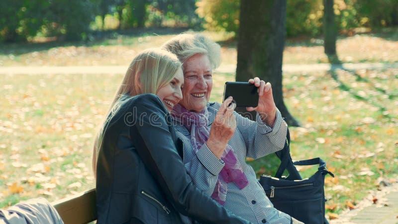 Zoom filmado por mulheres jovens e velhas fazendo selfie no smartphone no outono, em um belo parque fotos de stock royalty free
