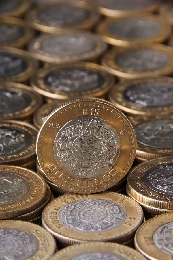 Zoom in moneda de diez pesos mexicanos sobre más monedas alineadas y apiladas, Toma vertical. Approach to ten Mexican pesos currency over more coins aligned stock images